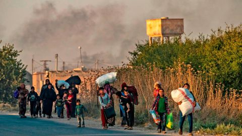 TOPSHOT - Civilians flee with their belongings amid Turkish bombardment on Syria's northeastern town of Ras al-Ain in the Hasakeh province along the Turkish border on October 9, 2019. - Turkey launched a broad assault on Kurdish-controlled areas in northeastern Syria today, with intensive bombardment paving the way for an invasion made possible by the withdrawal of US troops. (Photo by Delil SOULEIMAN / AFP) (Photo by DELIL SOULEIMAN/AFP via Getty Images)