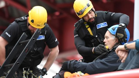 Police prepare to remove a climate change activist from the roof of a DLR train at Canary Wharf station.
