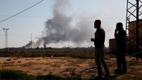 People in Akcakale, Turkey, watch smoke billow from inside Syria.