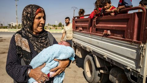 A woman holds a baby after arriving in Tal Tamr.