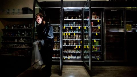 CVS Pharmacy shift supervisor James Quinn throws out ice cream from darkened freezers as downtown Sonoma, Calif., remains without power on Wednesday, Oct. 9, 2019. Pacific Gas and Electric has cut power to more than half a million customers in Northern California hoping to prevent wildfires during dry, windy weather throughout the region. (AP Photo/Noah Berger)