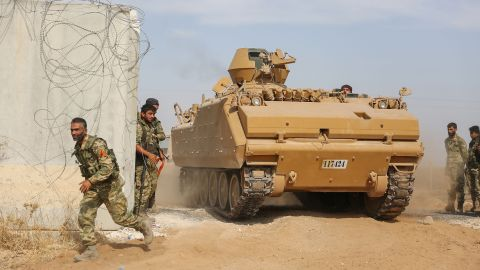 Pro-Turkish Syrian fighters drive an armored personnel carrier across the border into Syria on October 11.