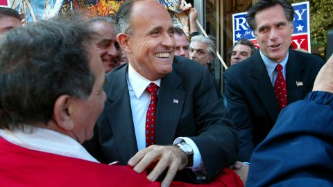 Giuliani greets people in Boston as he campaigns with Massachusetts gubernatorial candidate Mitt Romney, right, in October 2002.
