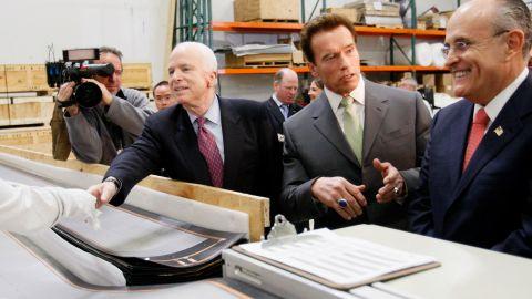 California Gov. Arnold Schwarzenegger talks to Giuliani as Giuliani and McCain tour a solar panel manufacturer in Los Angeles in January 2008.