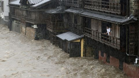 People watch floodwater from the Isuzu river flow by in Ise, Japan, on Saturday, October 12, 2019.