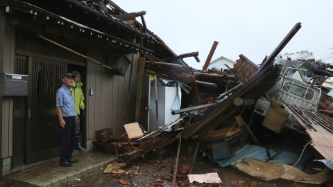 Residents survey damage caused by a suspected tornado in Ichihara, Japan, on October 12.