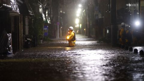 A rescue worker wades in floodwater in a residential area of Tokyo on October 12.