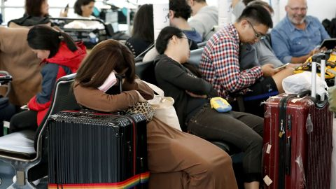 People sleep at the Haneda Airport in Tokyo on October 12. Flights were canceled on Saturday as Typhoon Hagibis approached the coast of Japan.
