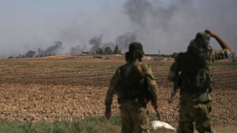 Turkish-backed Syrian fighters watch as smoke billows from the Syrian border town of Tal Abyad on October 12, 2019, as Turkey and its allies continue their assault on Kurdish-held border towns in northeastern Syria. - Ankara stepped up its assault on Kurdish-held border towns in northeastern Syria, defying mounting threats of international sanctions, even from Washington. (Photo by Bakr ALKASEM / AFP) (Photo by BAKR ALKASEM/AFP via Getty Images)