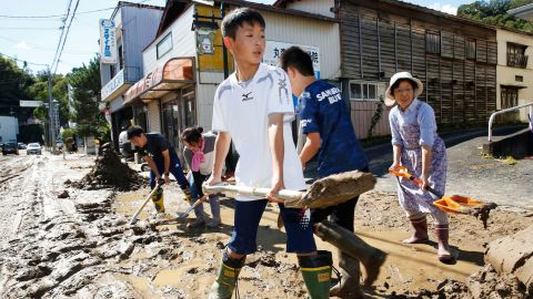 Students and residents scoop dirt and mud on October 13 as the town of Marumori, Japan, is flooded from the typhoon, which made landfall on Saturday.