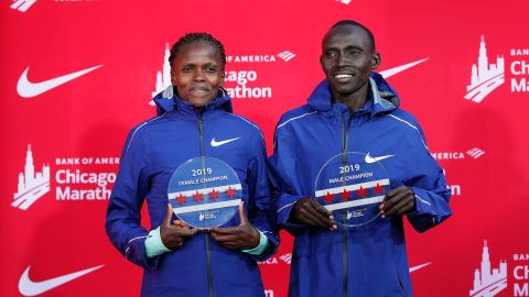 Kenya's Brigid Kosgei, left, and Lawrence Cherono smile as they hold their trophies.