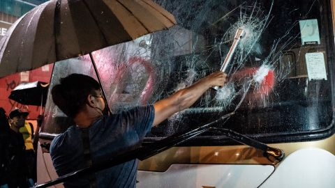 A protester attempts to break a tourist bus window on October 13.
