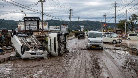 A car passes overturned vehicles in an area affected by flooding on October 14 in Nagano, Japan.