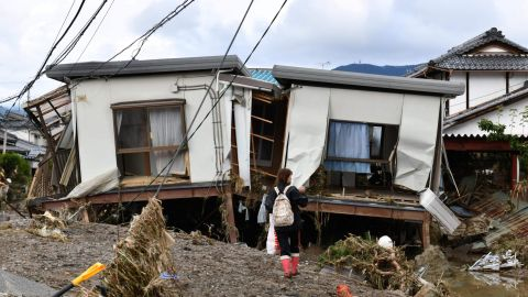 A woman looks at flood-damaged homes in Nagano on October 15, 2019, after high winds and torrential rain and triggered landslides and catastrophic flooding.