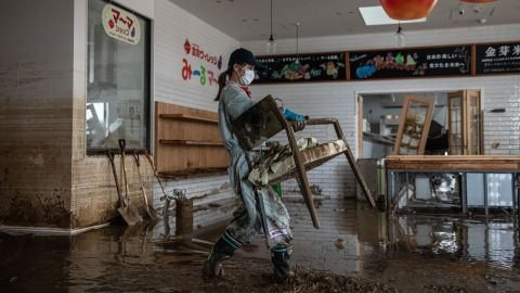 A woman helps to clear up a shop that was flooded during Typhoon Hagibis, on October 15, 2019 in Hoyasu near Nagano, Japan.