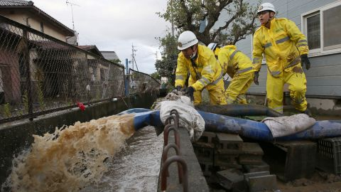 Firefighters pump water from a flooded area in the aftermath of Typhoon Hagibis in Nagano on October 15, 2019.