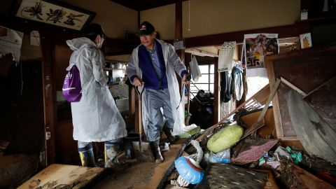 Toshio Yonezawa, 73, center, surveys his home with son, Yusuke, after Typhoon Hagibis passed through his neighborhood Tuesday, October 15, in Nagano, Japan.