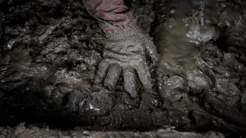 Yoshiki Yoshimura, 17, sifts through the mud for anything salvageable at his home destroyed by Typhoon Hagibis Tuesday.