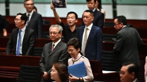 A pro-democracy lawmaker (behind) holds up a placard in protest as Hong Kong's Chief Executive Carrie Lam (C) walks into the chamber to give her annual policy address at the Legislative Council (Legco) in Hong Kong on October 16, 2019.