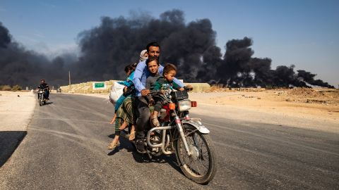 Displaced people, fleeing from the countryside of the Syrian Kurdish town of Ras al-Ain along the border with Turkey, ride a motorcycle together along a road on the outskirts of the nearby town of Tal Tamr on October 16, 2019 as they flee a deadly cross-border Turkish offensive that has sparked an international outcry, with smoke plumes of tire fires billowing in the background to decrease visibility for Turkish warplanes in the area. (Photo by Delil SOULEIMAN / AFP) (Photo by DELIL SOULEIMAN/AFP via Getty Images)