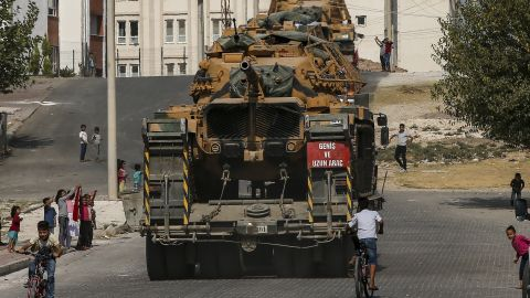 Local residents cheer as Turkish army tanks are transported on the outskirts of Akcakale, Turkey, on October 17.