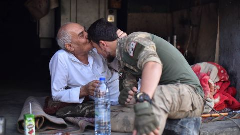 A local resident of Ras al-Ain kisses the forehead of a member of the Turkish-backed Free Syrian Army on October 17.