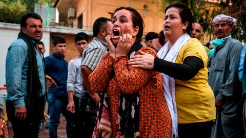 A woman reacts as a man's dead body arrives at a hospital in Ras al-Ain on October 18.