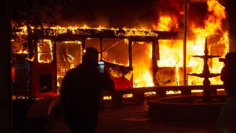 A bus burns in central Santiago on Friday in the wake of protests over fare hikes.