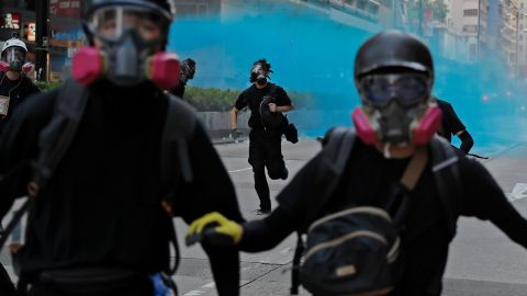 Police fire blue dye toward protesters in Hong Kong on Sunday, October 20. Blue dye can be used to stain and identify masked protesters.