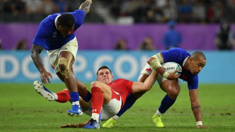 France's Gael Fickou battles for possession with Wales' Owen Watkin during quarterfinal at Oita Stadium.