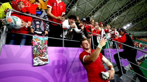 Wales' Dan Biggar takes selfies with fans at the end quarterfinal.