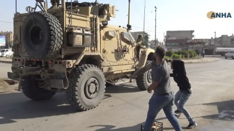 People angry over the US withdrawal hurl potatoes at American military vehicles as they pass through Qamishli on Monday, October 21. The image was taken from video provided by the Kurdish Hawar News Agency.
