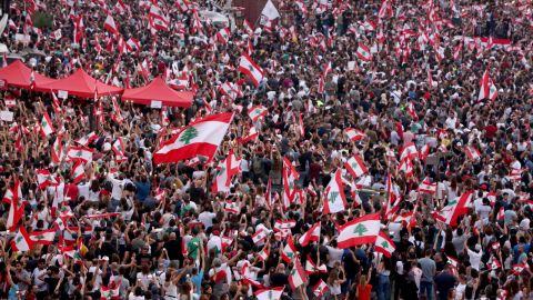 Demonstrators wave national flags during a rally in downtown Beirut on Sunday.