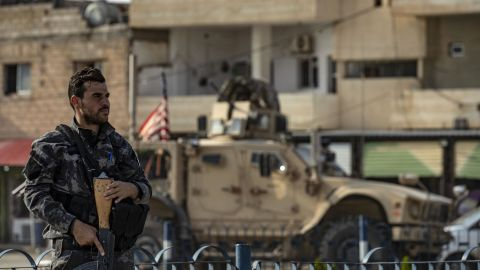 A fighter from the Syrian Democratic Forces SDF stands guard as a US military vehicle pulling out of a US forces base in the Northern Syrian town of Tal Tamr drives by.