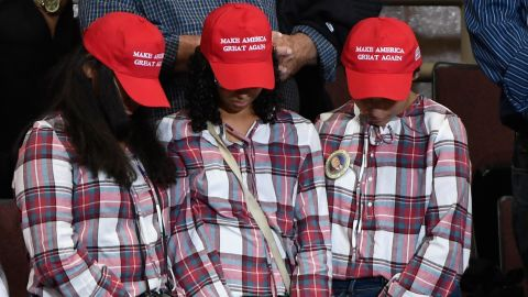 In this October 2018 file photo, three supporters bow their heads as a prayer is said at a campaign rally held by President Donald Trump in Rochester, Minnesota.