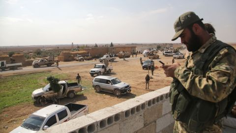 Turkey-backed Syrian fighters gather on a road between the northern Syrian towns of Tal Abyad and Kobani.