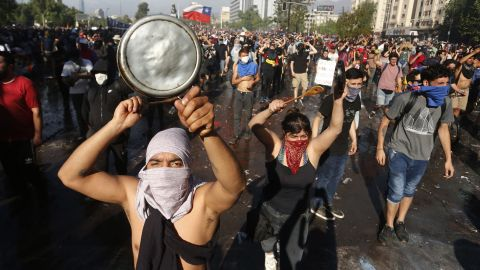 SANTIAGO, CHILE - OCTOBER 21: Demonstrators shouts slogans and display banners during a protest against Presidente Sebastian Piñera on October 21, 2019 in Santiago, Chile. President Sebastian Piñera suspended the 3.5% subway fare hike and declared the state of emergency for the first time since the return of democracy in 1990. Protests had begun on Friday and developed into looting and arson, generating chaos in Santiago, Valparaiso and a dozen other cities resulting in at least 8 dead.  (Photo by Marcelo Hernandez/Getty Images)