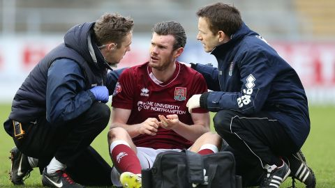 NORTHAMPTON, ENGLAND - FEBRUARY 06:  Zander Diamond of Northampton Town recieves treatment from physio Anders Braastad and Dr Andrew Odwell after a clash of heads which left him concussed during the Sky Bet League Two match between Northampton Town and York City at Sixfields Stadium on February 6, 2016 in Northampton, England.  (Photo by Pete Norton/Getty Images)