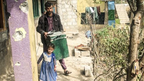 A little girl stands by her father as he clears rubbish in Jura, Neelum Valley, in Pakistani-administered Kashmir, on October 22, 2019.