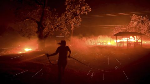 Susi Weaver, the manager for a ranch in the Mayacamas Mountains above Geyserville, California, sprays down the dry brush as the Kincade fire burns.