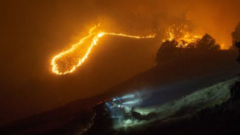 Crews build a fire break as the fast-moving blaze burns in the hills above the River Rock Casino near Geyserville.