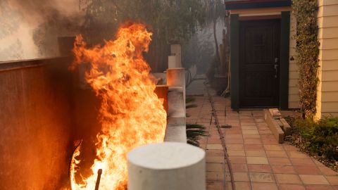 Flames burn close to an entrance of a home during the Tick fire in the Santa Clarita area of Los Angeles, Calif. on Thursday, Oct. 24, 2019(AP Photo/ Christian Monterrosa)