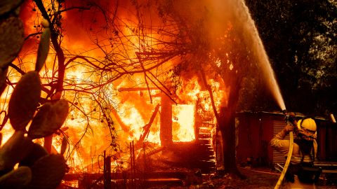 A firefighter sprays water on a burning home on Thursday.