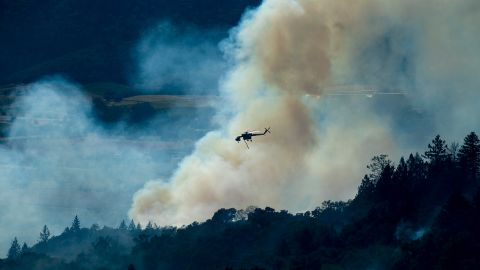 A helicopter passes a smoke plume on Thursday.