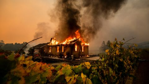 Vines surround a burning building as the Kincade Fire burns through the Jimtown community of unincorporated Sonoma County, California, on Thursday, October 24.