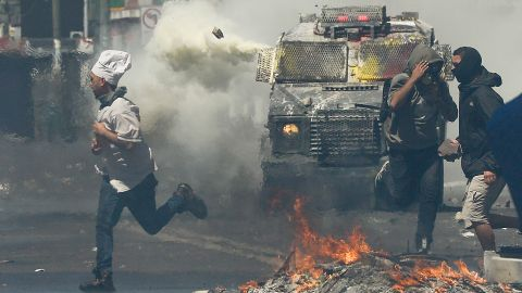 A man runs for cover as anti-government protesters clash with police in Valparaiso on Thursday.