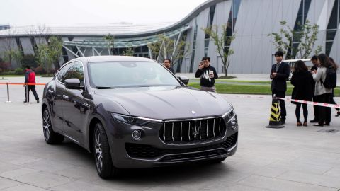 """This photo taken on March 23, 2016 shows people taking photos of a Maserati Levante sport-utility vehicle in Hangzhou, eastern China's Zhejiang province.  Chinese drivers are rushing to buy sport-utility vehicles in an """"arms race"""" for safety on the country's hair-raising roads, analysts say, as SUV sales hit the gas despite a slowing economy. / AFP / STR / China OUT / TO GO WITH AFP STORY CHINA-AUTO-SHOW-SUV,FOCUS BY BENJAMIN CARLSON        (Photo credit should read STR/AFP/Getty Images)"""