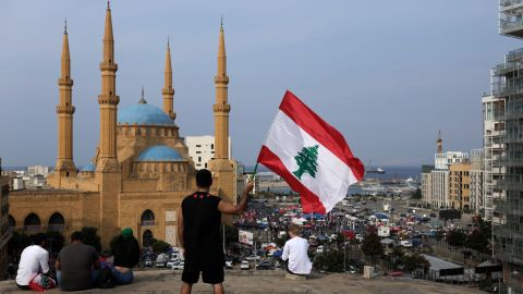 An anti-government protester holds up a Lebanese national flag during a protest in Beirut, Lebanon, Friday, Oct. 25, 2019. Leader of Lebanon's Hezbollah calls on his supporters to leave the protests to avoid friction and seek dialogue instead. (AP Photo/Hassan Ammar)