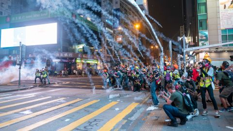 Tear gas smoke is seen exploding over reporters during an anti-government protest in Mong Kok district in Hong Kong on October 27.