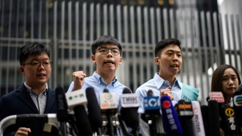 Pro-democracy activist Joshua Wong (second from left) and Kelvin Lam (second from right) shout slogans as they meet the media outside the Legislative Council (LegCo) in Hong Kong on October 29, 2019, after Wong was barred from standing in an upcoming local election.